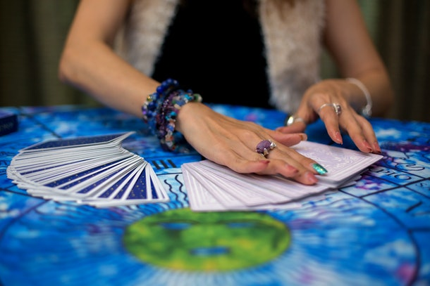 The fortune teller is using cards and crystal glass balls to see the fortune on the horoscope table.