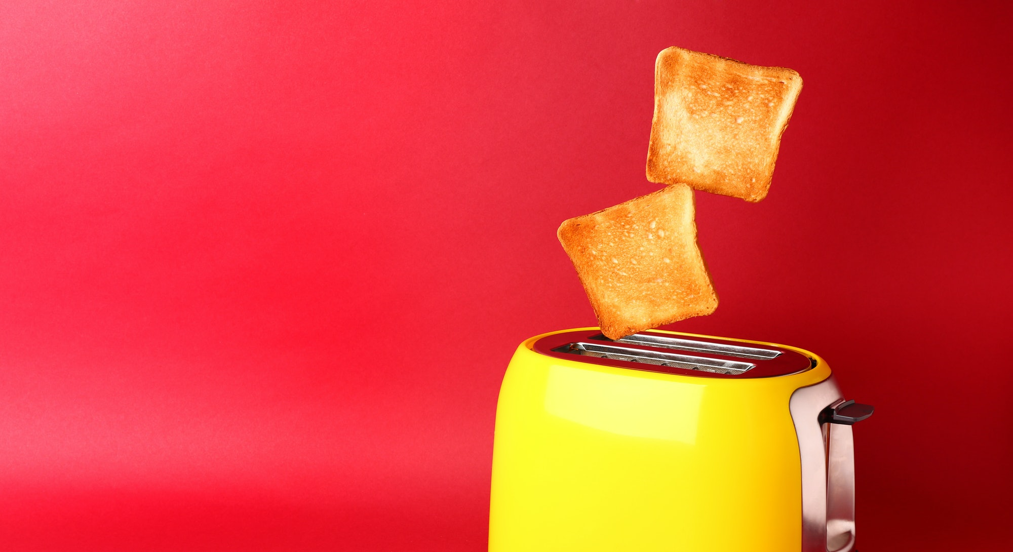 Toaster with bread slices on color background
