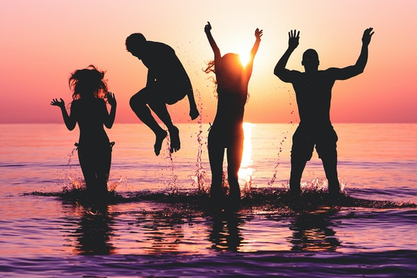 Four friends jump in the ocean at sunset.