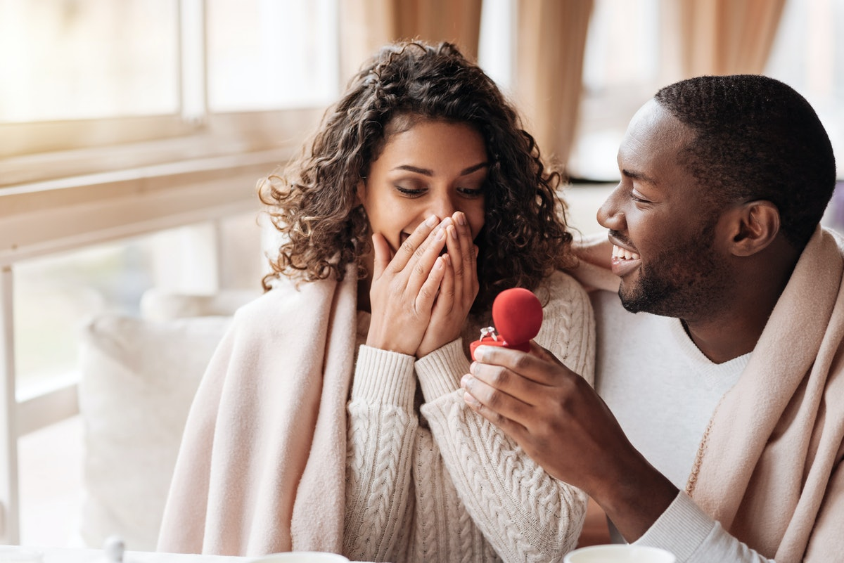 A happy and cozy couple gets engaged at home.