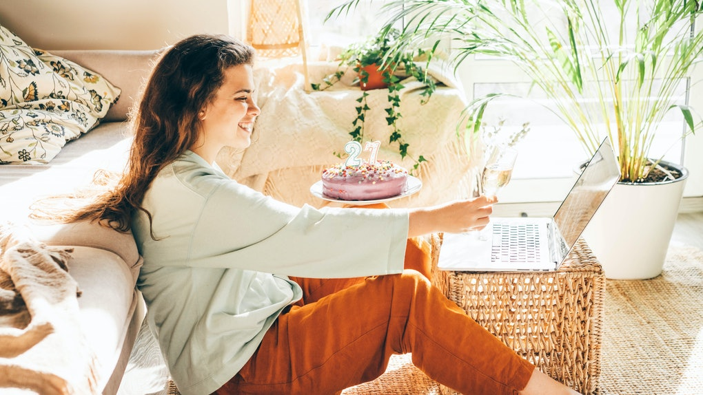 A woman holds her birthday cake while toasting to her friends on the computer.