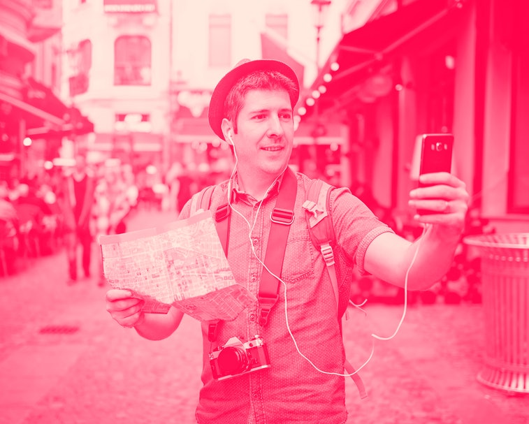 Travel Europe. Backpacker Traveler Man traveling alone on crowded streets in old town. Neck camera and holding city map in hand. Using video call on smart phone. Roam like home EU concept