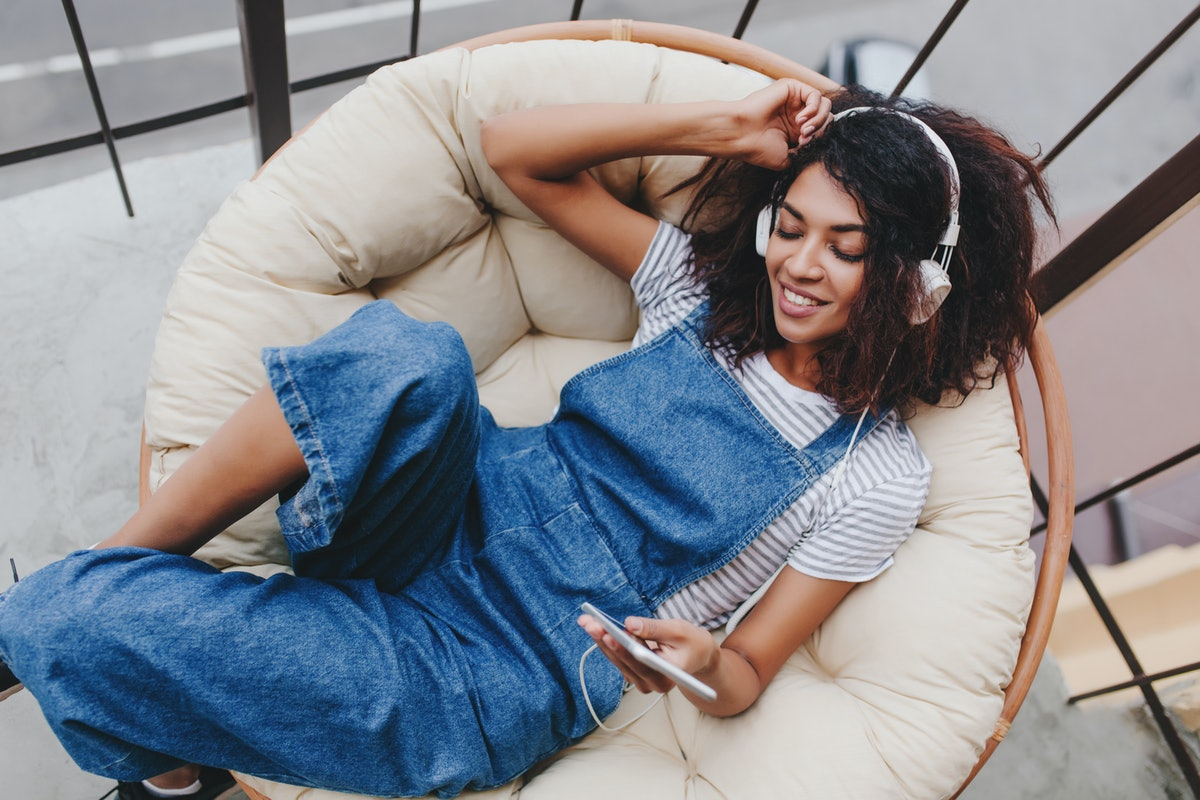 Blissful black young woman in vintage denim clothes chilling on terrace in white headphones. Attract...