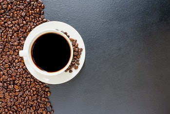 Black coffee in a cup of coffee and coffee beans placed on the old table Top view with empty space for your message