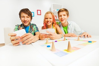 Happy teenagers playing table game holding cards