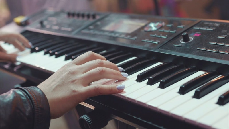 MIDI keyboard synthesizer piano keys. Stock. Woman playing the synthesizer. A music instrument background, music concept