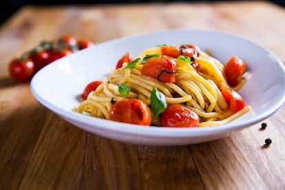 Fresh pasta with garlic Cherry Tomatoes and basil. Deliciosu  Pasta Plate. Raw vegan pasta. Spaghetti. Italian food. Italy. Roma. Fine dining. Healthy food. Fresca Pasta. Vegetarian