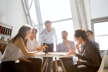 Cheerful diverse team people workers students laughing at funny joke while eating pizza together, friendly multi-ethnic colleagues group talking enjoying having fun and corporate lunch in office room