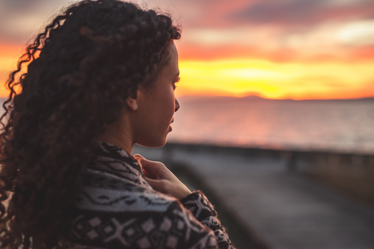 Young African American woman is standing on the promenade at the lake, looking thoughtfully towards the water and the setting sun. The girl in a vest is in a thoughtful mood