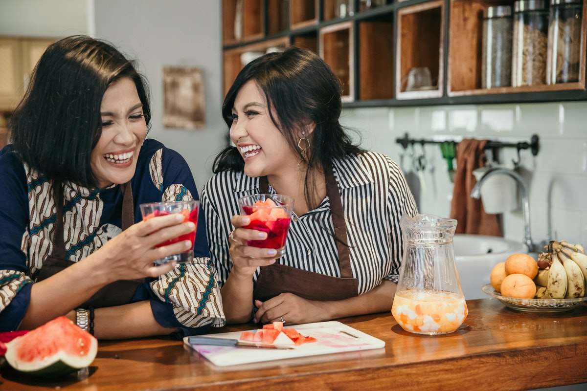 A happy mother and daughter share some cocktails together at home.