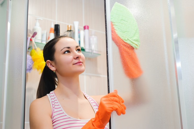 portrait of young woman cleaning shower door