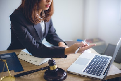 Lawyer sitting working with wooden gavel of judge and brass scale at the desk hand point working in ...