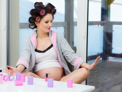 Pregnant woman with hair rollers getting nail treatment