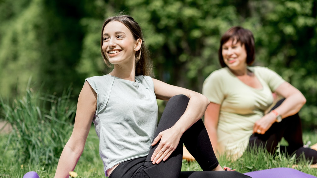 A mother and daughter enjoy doing some yoga outside on the grass.
