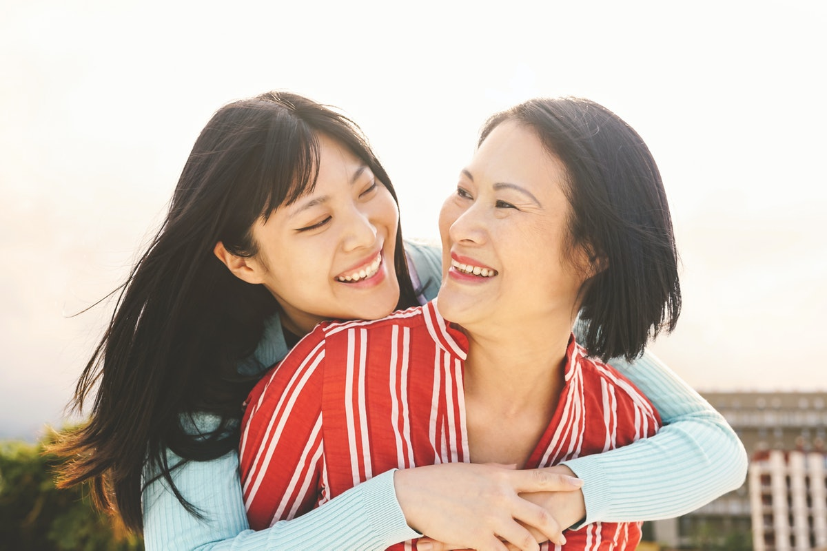 A happy asian mother and daughter smile, look at each other, and hug outside on a sunny day.