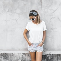 Hipster girl wearing blank white t-shirt and denim shorts posing against gray street wall, blank moc...