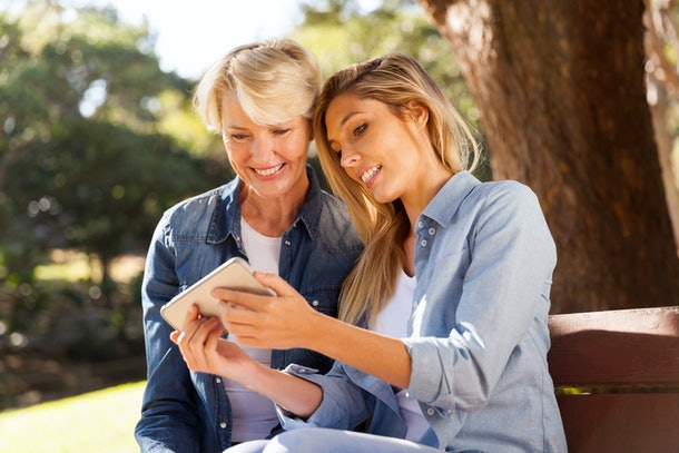 A blonde woman shows something on her cell phone to her mom while they sit on a bench in the sun.