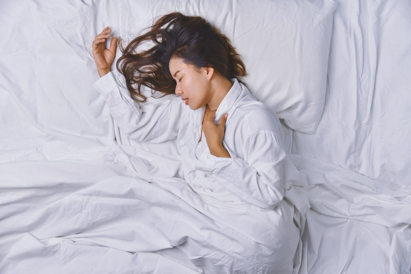 Young Woman Sleeping In Bed. Top view of young woman lying down sleeping well in bed. sleeping relax, young smiling pretty lady lies in bed.