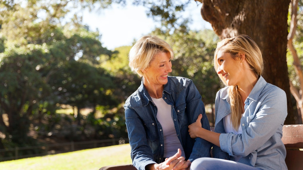A blonde mother and her daughter smile and chat on a bench in the sunshine.
