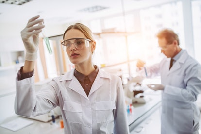 Two scientists are working in laboratory. Young female researcher and her senior supervisor are doin...