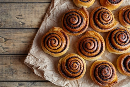 Freshly baked cinnamon buns with spices and cocoa filling on parchment paper. Top view. Sweet Homema...