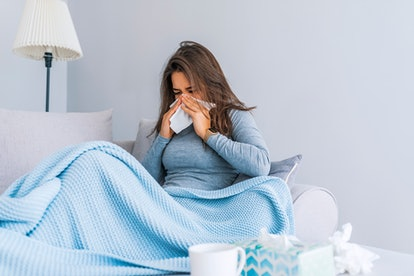 Sick Woman.Flu.Woman Caught Cold. Sneezing into Tissue. Headache. Virus .Medicines. Young Woman Infected With Cold Blowing Her Nose In Handkerchief. Sick woman with a headache sitting on a sofa