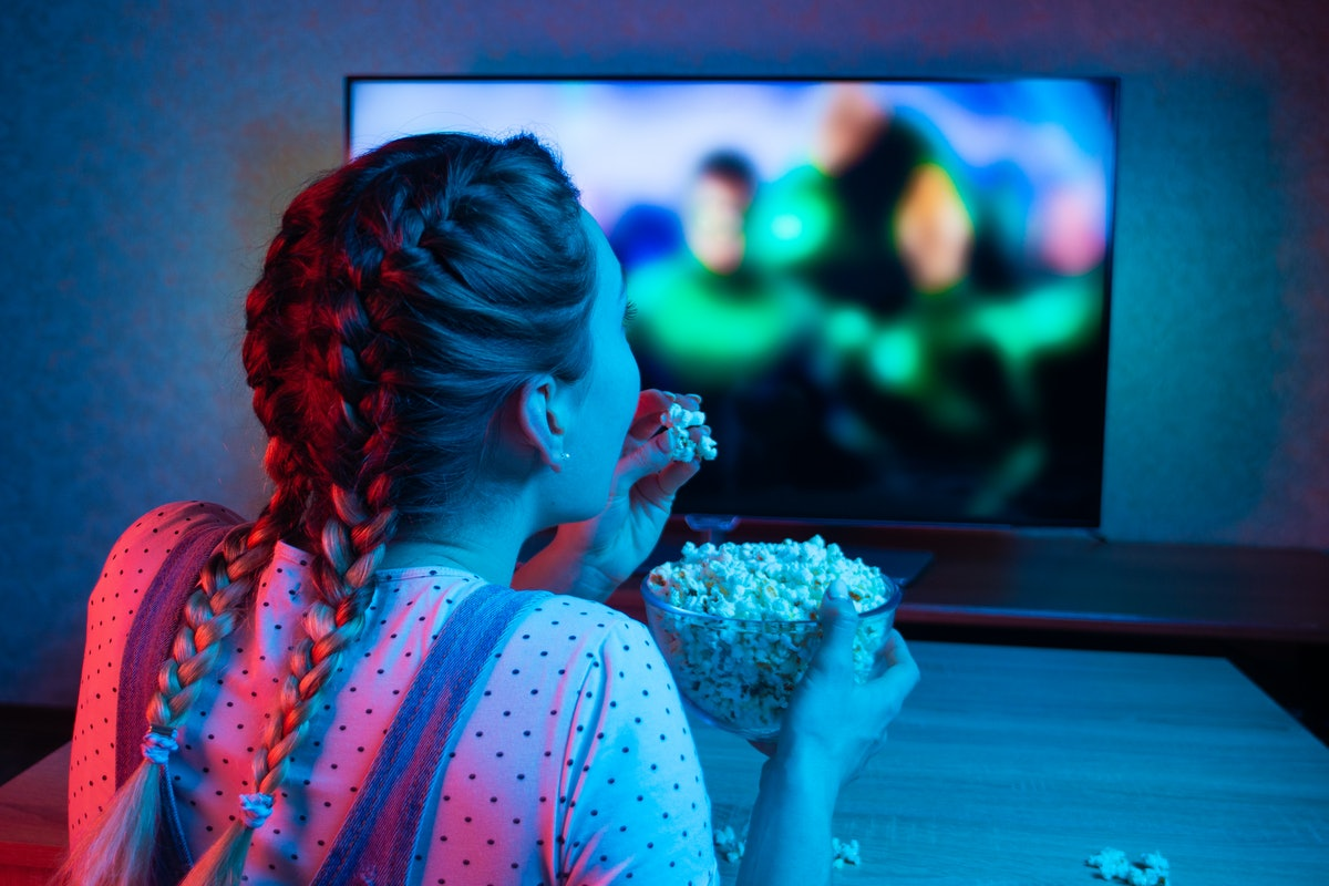 A young girl watching movies and eating popcorn with a bowl on the background of the TV. The color b...