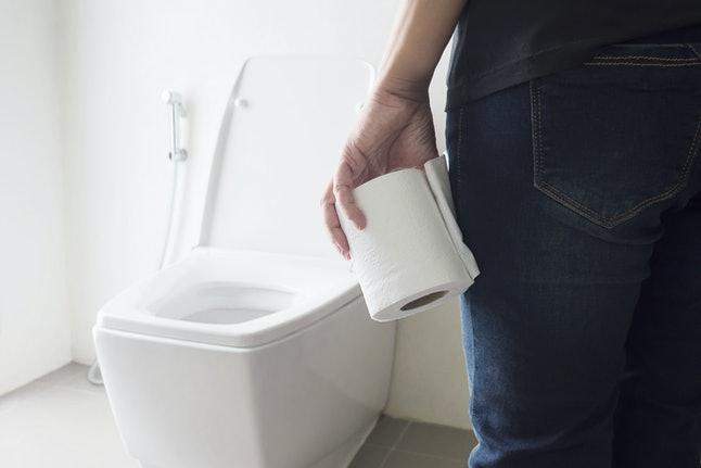Lady holding tissue near a toilet bowl