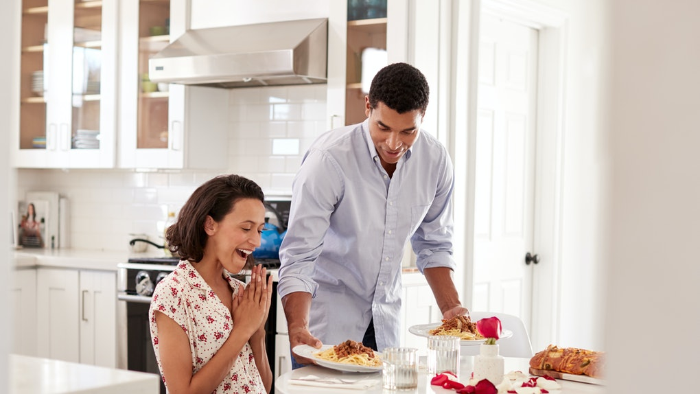 Young African American adult woman sitting at the table in the kitchen, her partner surprising her by serving a romantic meal, selective focus