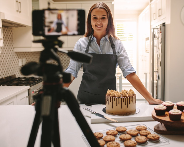 Woman recording video in her home kitchen. Pastry chef creating content for video blog.
