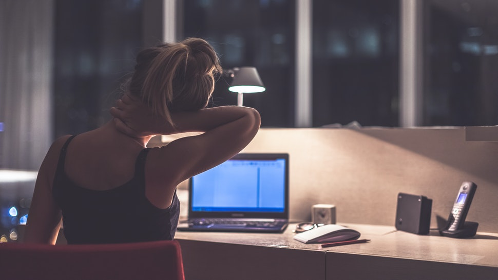 Young exhausted,depressed,concentrated woman sitting in her room or office with french windows  in the dark at the lamp.Studies late at night.Staying up late. Overworking. Feeling pain in the neck