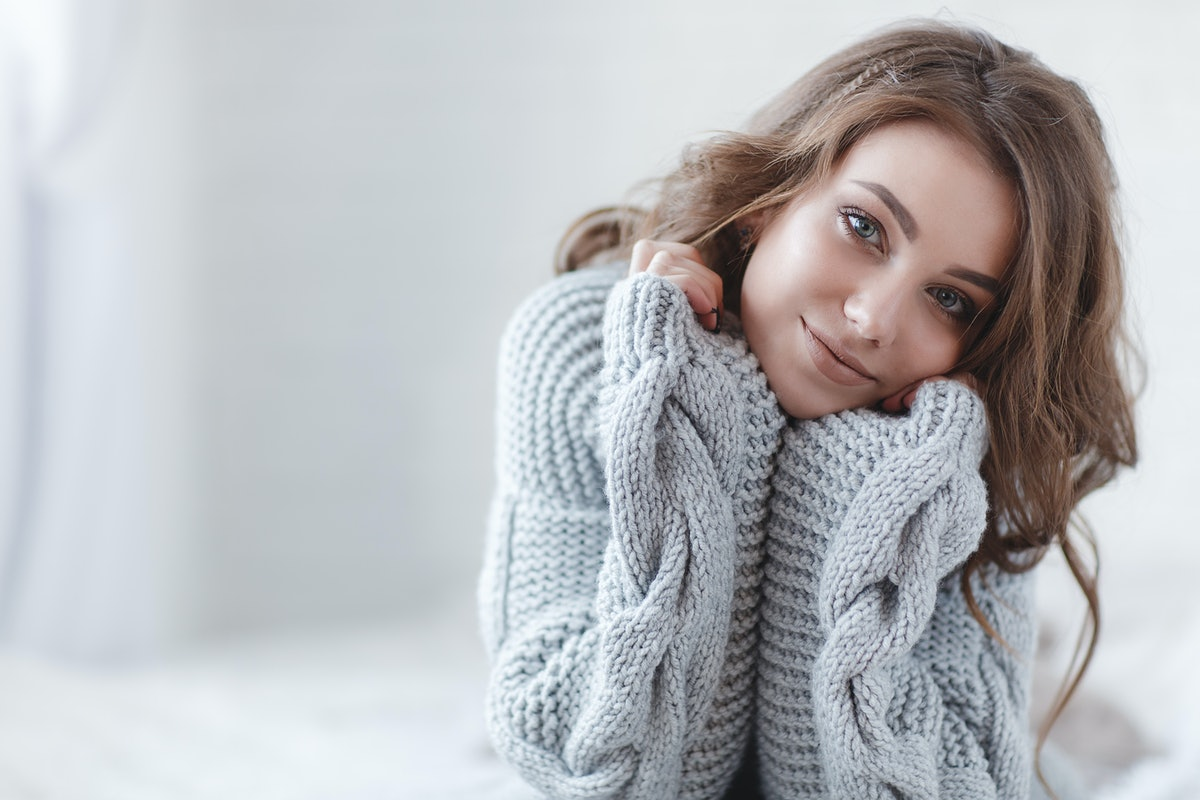 woman indoor portrait. Young beautiful woman in warm knitted clothes at home. fashion. Autumn, winte...