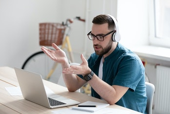 Focused young businessman in eyewear wearing headphones, holding video call with clients on laptop. Concentrated millennial man in glasses giving online educational class lecture, consulting customer.