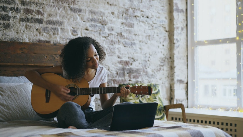 Curly african american teenager girl learning to play guitar using laptop computer sitting on bed at home