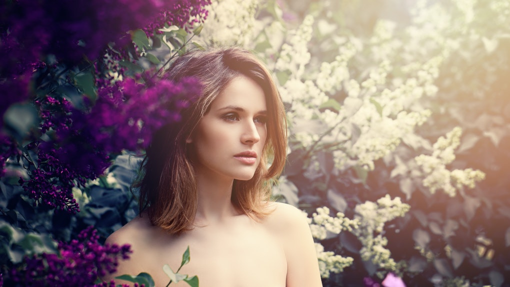 Fashion Model Girl with Long Bob Hair. Young Beautiful Woman with Healthy and Beauty Brown Hair on Flowers Background
