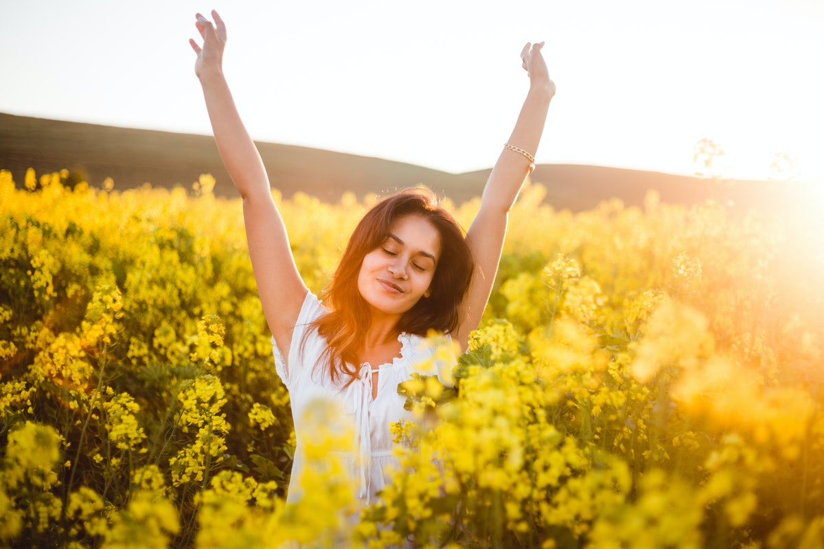 Teenage girl in yellow flowers field