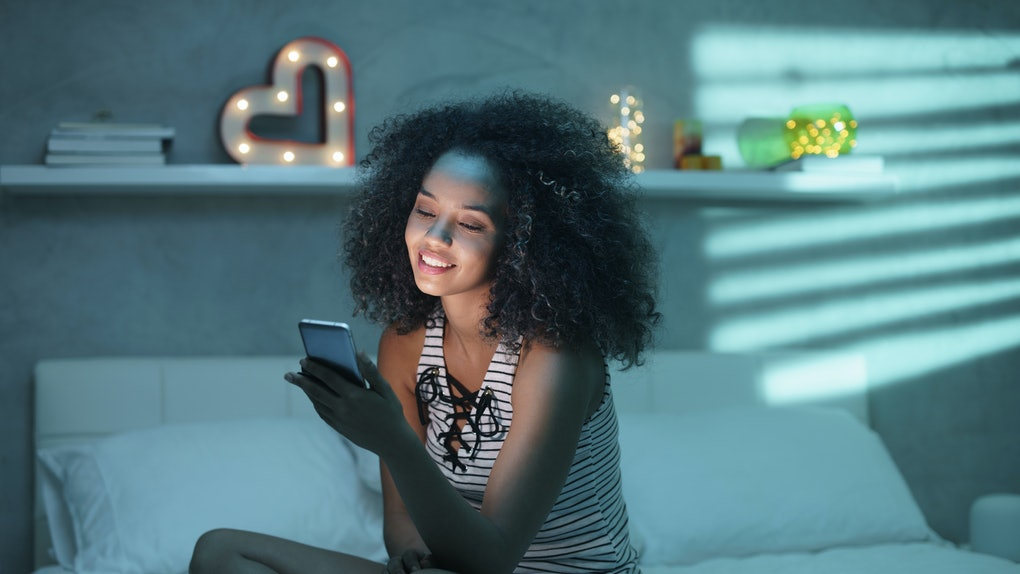 Happy african american teen in bed at home with smartphone. Young black woman watching funny video on mobile telephone in bedroom at night and laughing.
