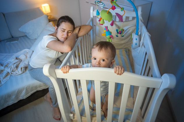 Tired mother falls asleep next to baby's crib