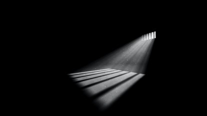A striking 3d illustration of jail window light in a completely dark prison cell. The rays of sun lo...