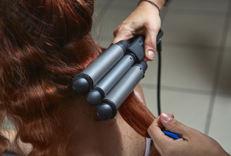 Young red haired woman having her hair curled with modern electric triple barrel curling iron in a hair styling salon. Closeup view.