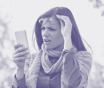 Annoyed upset woman in glasses looking at her smart phone with frustration while walking on a street on an autumn day