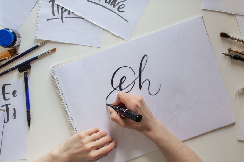 High angle view of Woman hands writing Oh words on white paper