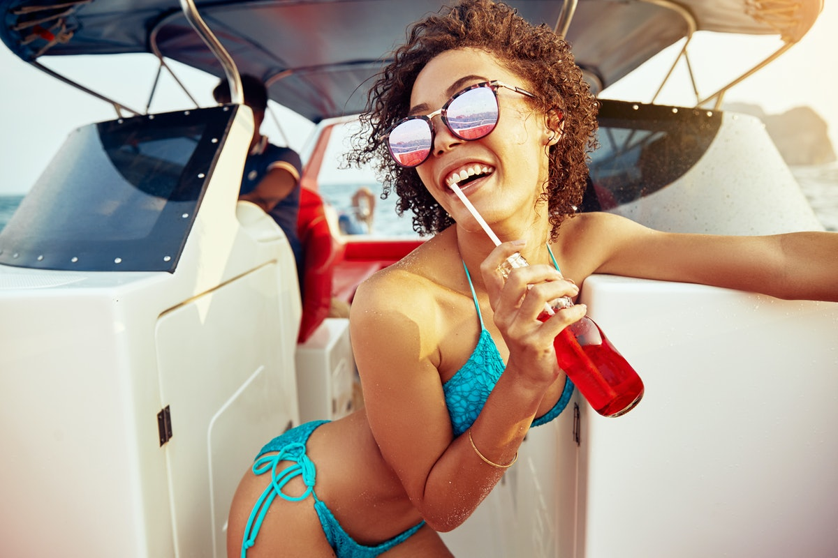 A happy brunette woman wearing sunglasses and a blue bikini sips a red drink on a boat in the summer.