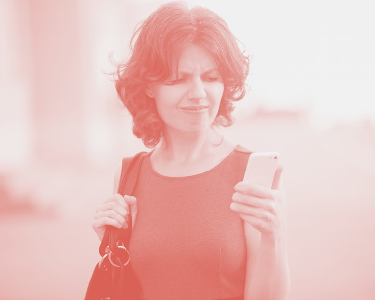 Portrait of annoyed stressed office young woman holding cellphone in hands on the city street in summer, looking at screen with cross face expression, mad at stressful texts and calls