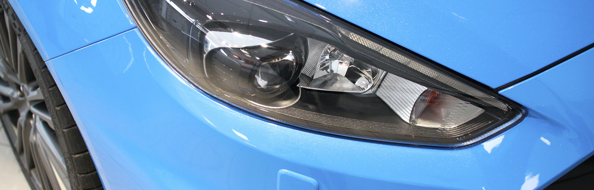 Front light and grill detail from a blue car in saloon