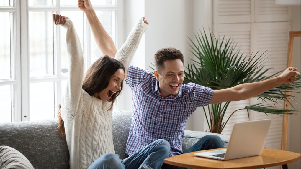 A happy couple celebrates together in front of their laptop with their arms' raised.