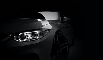 Grey new generic stylish sport coupe car with laser led headlight on dark black background. 3D render