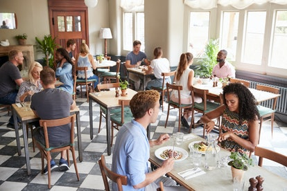 Customers Enjoying Meals In Busy Restaurant