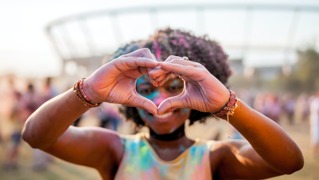 Beautiful African American girl at summer holi festival make heart symbol by hands