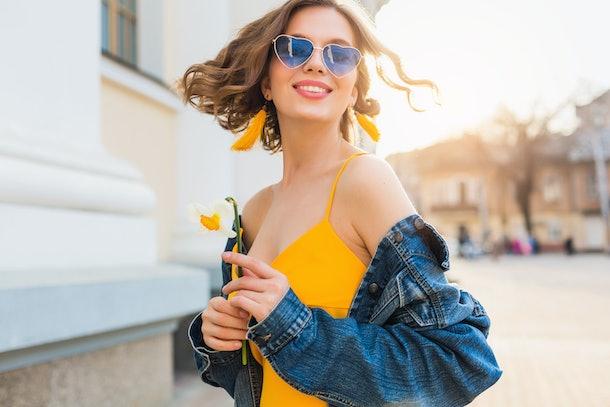 beautiful woman waving hair smiling, stylish apparel, wearing denim jacket and yellow top, fashion trend, summer style, happy positive mood, sunny day, sunrise, street fashion, blue sunglasses